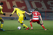 Joe Pigott of AFC Wimbledon has his shirt tugged  by Doncaster defender Tom Anderson  during the EFL Sky Bet League 1 match between Doncaster Rovers and AFC Wimbledon at the Keepmoat Stadium, Doncaster, England on 26 January 2021.