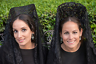 """Two young women wearing """"mantillas"""", the traditional head covering, in black lace, worn during the Semana Santa. Seville, Andalusia. Spain"""