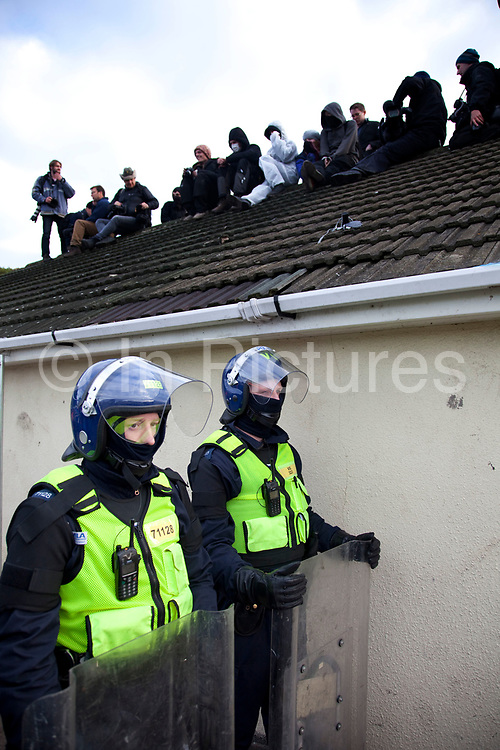 Protesters on the roof look down on lines of riot police. Travellers at Dale Farm site prior to eviction. Riot police and bailiffs were present on 20th October 2011, as the site was cleared of the last protesters chained to barricades. Dale Farm is part of a Romany Gypsy and Irish Traveller site in Crays Hill, Essex, UK<br /> <br /> Dale Farm housed over 1,000 people, the largest Traveller concentration in the UK. The whole of the site is owned by residents and is located within the Green Belt. It is in two parts: in one, residents constructed buildings with planning permission to do so; in the other, residents were refused planning permission due to the green belt policy, and built on the site anyway.