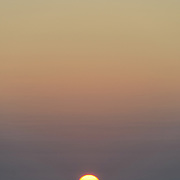The lays moments before the sun disappears below the horizon over the Pacific Ocean. Most of the frame is taken up by clear skies above ranging from orange to yellow. Taken at Swains Reef on the southern end of the Great Barrier Reef of the coast of Queensland, Australia.