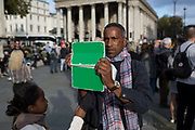 A visitor to London films a panoramic scene in Trafalagar Square with an electronic device with a well-used green protective cover, on 16th October 2018, in London, England.
