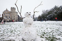 Windsor, UK. 24 January, 2021. A snowman stands arms aloft alongside the Long Walk in front of Windsor Castle following the first snowfall of the year. A spell of cold weather is expected to continue until Wednesday.