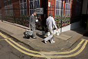 Two decorators walk past the construction hoarding belonging to Claridges in Mayfair, Westminster. Carrying work tools and paint pots from a nearby corner, they turn the corner with the image of railings, flowers and red brickwork - all fake - printed on to the temporary hoarding. One man has a cigarette in his mouth and his colleague turns to speak after they've finished work.