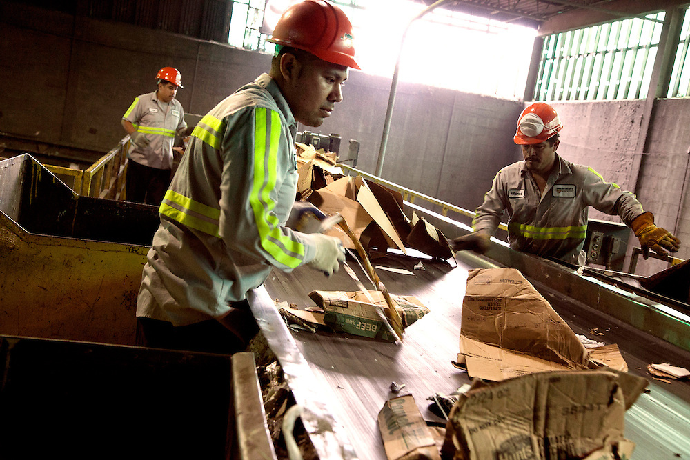 Sanitation Workers sorting waste Paper on conveyor belt at Paper Recycling Facility