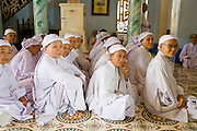 "10 MARCH 2006 - TAY NINH, VIETNAM: Women members of the Cao Dai religion wait to pray before noon services at the Cao Dai Main Temple in Tay Ninh. The Cao Dai complex in Tay Ninh is the sect's headquarters. The Cao Dai religion is a blending of Buddhism, Confucianism, Taoism, Christianity and Islam. There ""saints""  include Chinese leader Sun Yat Sen and French author Victor Hugo. There are about two million members of the Cao Dai religion in Vietnam. British author Graham Greene, who wrote about the Cao Dai in the ""The Quiet American"" said the relegion was ""a Walt Disney fantasia of the East."" Photo by Jack Kurtz / ZUMA Press"