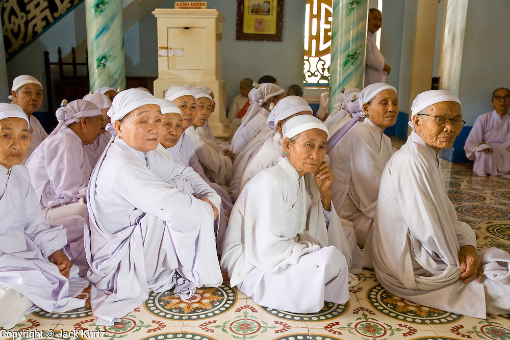 """10 MARCH 2006 - TAY NINH, VIETNAM: Women members of the Cao Dai religion wait to pray before noon services at the Cao Dai Main Temple in Tay Ninh. The Cao Dai complex in Tay Ninh is the sect's headquarters. The Cao Dai religion is a blending of Buddhism, Confucianism, Taoism, Christianity and Islam. There """"saints""""  include Chinese leader Sun Yat Sen and French author Victor Hugo. There are about two million members of the Cao Dai religion in Vietnam. British author Graham Greene, who wrote about the Cao Dai in the """"The Quiet American"""" said the relegion was """"a Walt Disney fantasia of the East."""" Photo by Jack Kurtz / ZUMA Press"""