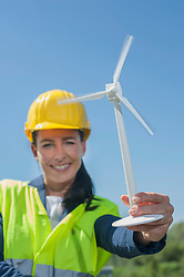 Female engineer showing wind turbine at geothermal power station, Bavaria, Germany