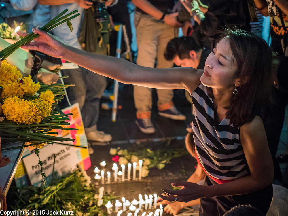 18 AUGUST 2015 - BANGKOK, THAILAND:  A woman reaches for flowers at a makeshift memorial in front of Erawan Shrine, which was damaged by a bomb Monday night. An explosion at Erawan Shrine, a popular tourist attraction and important religious shrine in the heart of the Bangkok shopping district, killed at least 20 people and injured more than 120 others, including foreign tourists, during the Monday evening rush hour. Twelve of the dead were killed at the scene. Thai police said an Improvised Explosive Device (IED) was detonated at 18.55. Police said the bomb was made of more than six pounds of explosives stuffed in a pipe and wrapped with white cloth. Its destructive radius was estimated at 100 meters.     PHOTO BY JACK KURTZ