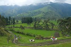tourists riding horses through fields below mountains with cloudforest,Zuleta, Ecuador, South America.  MR