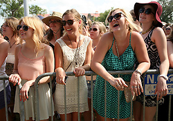 29 April 2012. New Orleans, Louisiana,  USA. <br /> New Orleans Jazz and Heritage Festival. <br /> Young women enjoying the music.<br /> Photo Credit; Charlie Varley/varleypix.com
