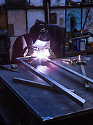 Welder Joshua Sanchez welding an aluminum frame for a food cart canopy. The carts are made of stainless steel inside and out, but the canopies are framed with aluminum to save weight.
