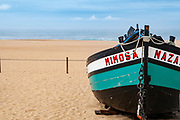Traditional green and black wooden Portuguese fishing boat on the beach of Nazare, Portugal. These boats are on display by the Dry Fish Museum