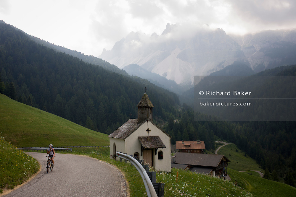 Cyclist climbs past hamlet chapel with presence of huge Dolomites mountains of the Puez Geisler range in the south Tyrol, Italy.