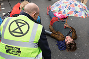 A female Extinction Rebellion protesters who has clued herself to the road at Trafalgar Square on the 7th October 2019 in Central London in the United Kingdom. Extinction Rebellion protesters occupy locations across central London including Westminster Bridge, Whitehall and Trafalgar Square in a wave of protests planned to continue for 2 weeks.