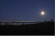 Salisbury Mills, New York - A train crosses the Moodna Viaduct railroad trestle as an almost full moon rises in the background on Nov. 20, 2010.