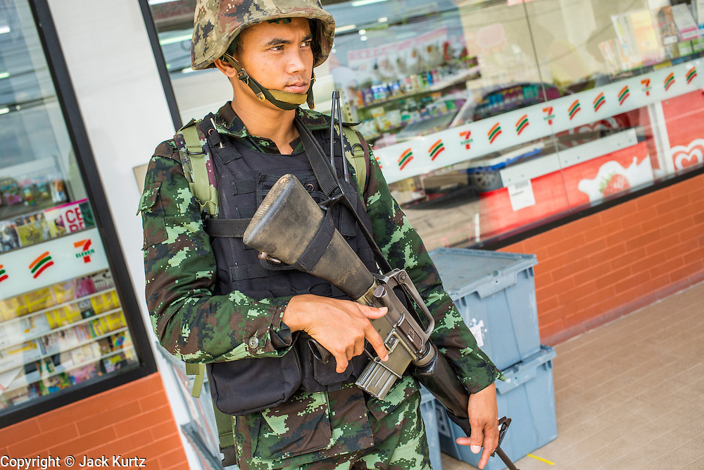 """25 OCTOBER 2012 - TAK BAI, NARATHIWAT, THAILAND: A soldier in the Royal Thai Army on duty in front of a 7-11 convenience store in Tak Bai, Thailand. The """"Tak Bai Incident"""" took place on Oct. 25 in Tak Bai, Narathiwat, Thailand during the Muslim insurgency in southern Thailand. On that day, a crowd gathered to protest the arrest of local residents. Police made hundreds of arrests during the protest and transported the arrested to Pattani, about two hours away, in another province. They were transported in locked trucks and more than 80 people suffocated en route. This enraged local Muslims and shocked people across Thailand. No one in the Thai army accepted responsibility for the deaths and no one was ever charged. In the past, the anniversary of the incident was marked by protests and bombings. This year it was quiet. More than 5,000 people have been killed and over 9,000 hurt in more than 11,000 incidents, or about 3.5 a day, in Thailand's three southernmost provinces and four districts of Songkhla since the insurgent violence erupted in January 2004, according to Deep South Watch, an independent research organization that monitors violence in Thailand's deep south region that borders Malaysia.   PHOTO BY JACK KURTZ"""