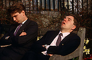 Snatching a well-earned lunchtime snooze, two young office workers in Trinity Park in the City of London. The young man on the left has his arms folded across his chest, his dark pinstripe suit apparently a little warm on this fine day. To his left is another youngish gentleman who looks less formal: his jacket opened and his tie crooked while his open mouth might emit snores in this public space. The bench which is owned by the Corporation of London has pigeon droppings on the back and arm rest but these two tired people care less about animal hygiene than the chance to steal a few precious minutes sleep before re-entering their office buildings and returning to desks.