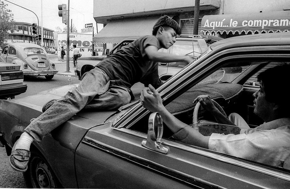 Homeless boy making a living by washing car windscreens, Oaxaca, Mexico. 1996