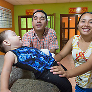 CAPTION: Since frequent visits to Hospital Escuela are required for Keren's speech therapy, she and her parents - who are low earners - need support with accommodation and meals. Fundación Abrigo has therefore come to their aid. The NGO has two shelter houses adjacent to the two largest hospitals in Honduras, including Hospital Escuela in Tegucigalpa. It offers free shelter for patients and family members that come to these two hospitals due to a lack of sufficient healthcare in their home towns and villages. Fundación Abrigo is the only place that offers, at no cost, not only a pleasant and safe place to sleep and rest but also provides the patients and their families with three free meals a day. LOCATION: Fundación Abrigo, Boulevard Sujapa, Tegucigalpa, Honduras. INDIVIDUAL(S) PHOTOGRAPHED: From left to right: Keren Sarahi Mijango Iriarte, Jaime Mijango Mejia and Maria Isabel Iriarte Hernandez.