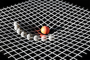 The motion of a planets orbit around a star is simulated by rolling a ball on a curved surface of plastic..