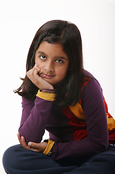 Young girl sitting cross legged on the floor with hand under chin,