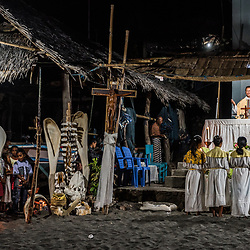 """Leva (Ocean) Season Opening Ceremony<br /> <br /> With the arrival of the twilight, the blend of spirit superstition and world religion becomes more visible, as the Catholic mass is about to start. The tiny chapel has been festively decorated with polished whale spines and a skull which had to be carried by not less than a dozen men. Tonight, the bishop reminds the villagers that bad deeds will upset their ancestors and therefore almost logically cause bad results, in contrast, all good deeds will help to pursue a blissful life. The ancestors are of higher importance because it's them who will carry all wishes of the Lamalerans to God. <br /> <br /> Before the Corpus Christiwill be shared among the people led by the hymns of a local chorus, the bishop calls out the names of the fishermen who died on duty. Like the crew members from the Batafor Clan who vanished in 1925 after going on a hunt. Their boat had been found but not the crew. Yes, even if quite rare, there is death in this business of whaling. The ceremony ends with the fading flicker of candle lights which the Lamalerans have been sending to sea as offerings for their ancestors.<br /> <br /> Before the Catholic missionaries arrived in Lamalera, the villagers believed in Lara Wulan """"the god of the sky"""", Tana Ekan """"the god of the earth"""" and """"Ina Leva"""" the mother of the sea. Additionally they were worshipping their ancestors (which became saints with the rise of Christianity). These forefathers are responsible to faithfully carry the wishes to Lara Wulan. The priests made them believe that water has been created by God. This has been was accepted, as it was quite easy to replace Ina Leva by holy Mother Mary. Ina Leva alias Mother Mary together with their ancestral saints will always prepare food for this village – which are the whales."""