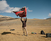 """Paul cleaning his tent. Life in our camp below the Aqbelis Pass, in the Little Pamir range. Guiding and photographing Paul Salopek while trekking with 2 donkeys across the """"Roof of the World"""", through the Afghan Pamir and Hindukush mountains, into Pakistan and the Karakoram mountains of the Greater Western Himalaya."""