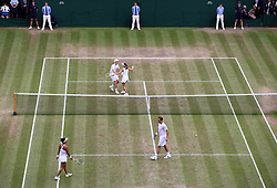 Martina Hingis and Jamie Murray (top of court) celebrate during the mixed doubles final against Heather Watson and Henri Kontinen on day thirteen of the Wimbledon Championships at The All England Lawn Tennis and Croquet Club, Wimbledon.