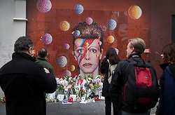 © Licensed to London News Pictures. 10/01/2017. London, UK. Fans stand at a mural and shrine to David Bowie in Brixton. David Bowie who died a year ago today, was born in Brixton, south London. Photo credit: Peter Macdiarmid/LNP