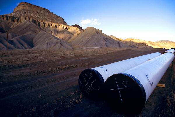 Oil and gas pipelines laying on ground of arid landscape near mountains.
