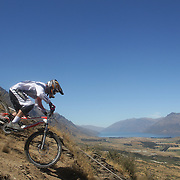 Connor Sandri from Oamaru in action during the NZBNZ South Island Downhill Cup mountain bike downhill series held on The Remarkables face with a stunning backdrop of the Wakatipu Basin. 150 riders took part in the two day event.  Queenstown, Otago, New Zealand. 9th January 2012. Photo Tim Clayton