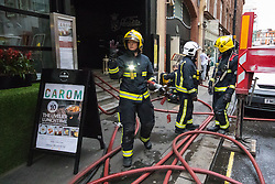 Soho, London, May 8th 2015. Firefighters deal with a fire that broke out at lunchtime in the kitchens of Carom and Floridita, a pair of Wardour Street restaurants in the heart of Soho. The cause is still being investigated.