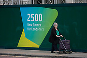 An elderly south Londoner walks past a regeneration project hoarding at Elephant Park, Elephant & Castle, on 11th October 2016, in London, England. London borough of Southwark. Southwark Council's development partner, Lendlease is regenerating over 28 acres across three sites at the heart of Elephant & Castle, in what is the latest major regeneration opportunity in zone 1 London. The vision for the £1.5 billion regeneration is to build on the area's strengths and vibrant character in order to re-establish Elephant & Castle as one of London's most flourishing urban quarters. The Elephant & Castle regeneration is of a scale rarely seen in central London and includes almost 3,000 new homes, plus office, retail, community, leisure and restaurant space.