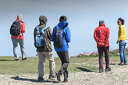A group of walkers on a windy East Pentire Headland in Newquay, Cornwall.