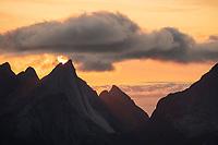 July summer sun setting over peaks of Breiflogtind from summit of Reinebringen, Reine, Moskenesøy, Lofoten Islands, Norway