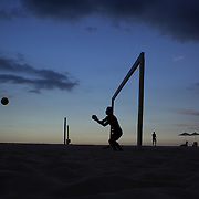 Locals play football at sunset on Copcabana beach, Rio de Janeiro,  Brazil. 5th July 2010. Photo Tim Clayton..The beaches of Rio de Janeiro, provide the ultimate playground for locals and tourists alike. Beach activity is in abundance as beach volley ball, football and a hybrid of the two, foot volley, are played day and night along the length and breadth of Rio's beaches. .Volleyball nets and football posts stretch along the cities coastline and are a hive of activity particularly at it's most famous beaches Copacabana and Ipanema. .The warm waters of the Atlantic Ocean provide the ideal conditions for a variety of water sports. Walkways along the edge of the beaches along with exercise stations and cycleways encourage sporting activity, even an outdoor gym is available at the Parque Do Arpoador overlooking the ocean. .On Sunday's the main roads along the beaches of Copacabana, Leblon and Ipanema are closed to traffic bringing out thousands of people of all ages to walk, run, jog, ride, skateboard and cycle more than 10 km of beachside roadway. .This sports mad city is about to become a worldwide sporting focus as they play host to the world's biggest sporting events with Brazil hosting the next Fifa World Cup in 2014 and Rio de Janeiro hosting the Olympic Games in 2016...