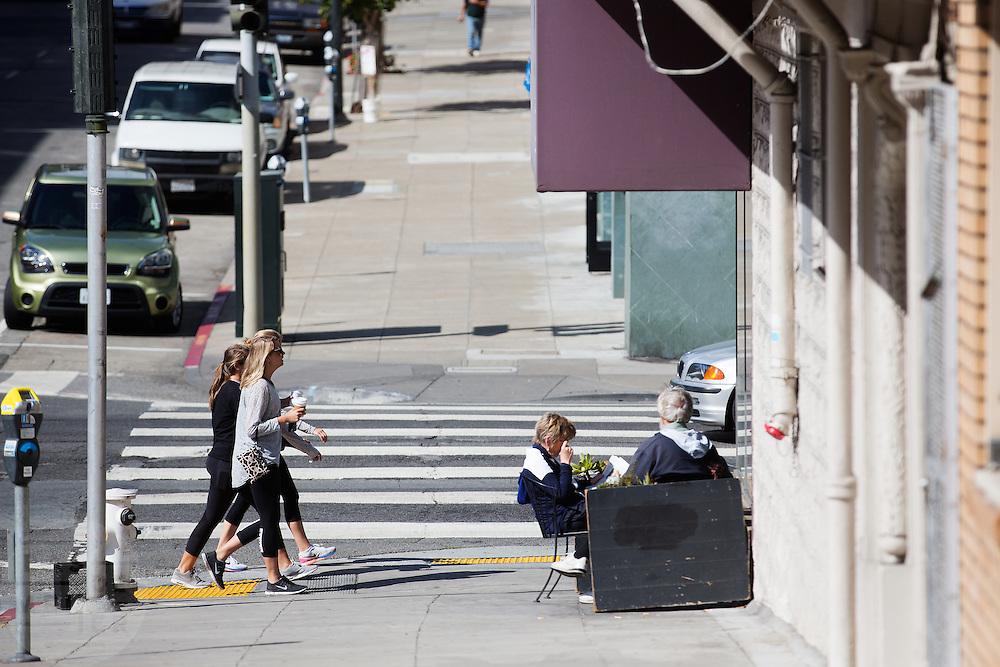 Voetgangers met koffie in de hand passeren een terrasje. De Amerikaanse stad San Francisco aan de westkust is een van de grootste steden in Amerika en kenmerkt zich door de steile heuvels in de stad.<br /> <br /> Pedestrians with coffee on the go pass a terrace. The US city of San Francisco on the west coast is one of the largest cities in America and is characterized by the steep hills in the city.