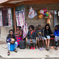 Lilian Mutheu (centre with red shirt) is a mentor in the Dreams project in Nairobi, Kenya. Here she sits with other mentors of the programme in the street in Pipeline district of Nairobi.<br /> <br /> DREAMS is an acronym for Determined, Resilient, Empowered, AIDS-free, Mentored, and Safe women. The project aims to empower girls and young women between 10 and 24 years around issues including HIV prevention, contraceptive methods, health, education and social economic intervention.<br /> <br /> Lilian, who is mother, is familiar with some of the issues through her own personal experience and provides guidance and support to hundreds of young women and girls in the extensive slum of Makuru Kwa Njenga in Nairobi.
