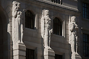Mythical Greek male telamon figures look towards a female caryatid sculpture on the exterior of the Bank of England, on 15th August 2016 in the City of London, UK. The Bank of England, is the central bank of the United Kingdom and the model on which most modern central banks have been based. Established in 1694, it is the second oldest central bank in the world. Sir Herbert Bakers rebuilding of the Bank, demolishing most of Sir John Soanes earlier building, was described by architectural historian Nikolaus Pevsner as the greatest architectural crime, in the City of London, of the twentieth century.