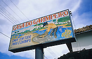 GOLD MINERS, Amazon, Venezuala, South America. Hotel with sign. Ecological biosphere and fragile ecosystem where flora and fauna, and native lifestyles are threatened by progress and development. The rainforest is home to many plants and animals who are endangered or facing extinction. This region is home to indigenous primitive and tribal peoples including the Yanomami and Macuxi. Sign says: Casa do garimpeiro, onde tem tudo para o garimpo. Goldminers home.