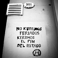 """Translation """"WE DO NOT WANT BANK HOLIDAYS, WE WANT TO ABOLISH THE STATE """"<br /> <br /> Buenos Aires, Argentina March 2006<br /> Protest, resistance and memory:  The Stencil images in Buenos Aires. <br /> The stencil art takes the streets of the Argentinian capital. Urban artists bomb in silence the city with messages that combine political and social content, imagination and irony.<br /> Photo: Ezequiel Scagnetti"""