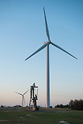 Oil pump jack and wind turbines at sunset in central Oklahoma near Calumet.
