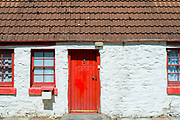 Quaint traditional whitewashed cottage with bright red front door and windows in Argyll and Bute, Scotland