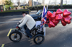 © Licensed to London News Pictures. 14/02/2019. London, UK. A Pro Brexit campaigner rides a bike with heart shaped  balloons attached to it, outside the Houses of Parliament in Westminster, on the day that MPs are due to take part in further debates and votes on Brexit. A series of amendments are being tabled to try to change the direction of Brexit, but a vote on a deal will not be held today as was originally planned. Photo credit: Ben Cawthra/LNP