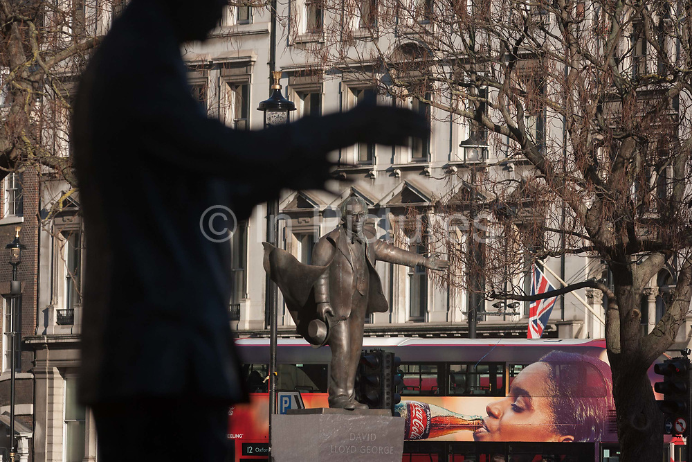 A Coca-Cola bus ad and the grasping arms of SouthAfrican President Nelson Mandelas statue with outstretched arm of former Labour politician David Lloyd-George Statues on 18th January 2017, in Parliament Square, London England. The statue of David Lloyd George is an outdoor bronze sculpture of former British Prime Minister David Lloyd George by Glynn Williams. This statue, which stands 8 feet 2.4 m tall, was unveiled in October 2007 and was funded by the David Lloyd George Statue Appeal, a charitable trust supported in part by HRH The Prince of Wales. The memorial to Nelson Mandela in Parliament Square, London, is a bronze sculpture of former President of South Africa and anti-apartheid activist Nelson Mandela. Originally proposed to Mandela by Donald Woods in 2001, a fund was set up and led by Woodss wife and Lord Richard Attenborough.