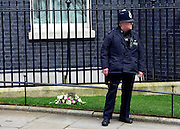 © Licensed to London News Pictures. 10/04/2013. Westminster, UK. Policemen with flowers left in memory of Margaret Thatcher on Downing Street today. David Cameron British Prime Minister leaves Downing Street today for a special session of recalled parliament to discuss the recent death of Margaret Thatcher . Photo credit : Stephen Simpson/LNP