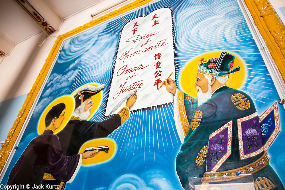 """29 MARCH 2012 - TAY NINH, VIETNAM:  The main entrance of the Cao Dai prayer hall at the Cao Dai Holy See in Tay Ninh, Vietnam. Cao Dai (also Caodaiism) is a syncretistic, monotheistic religion, officially established in the city of Tây Ninh, southern Vietnam in 1926. Cao means """"high"""" and """"Dai"""" means """"dais"""" (as in a platform or altar raised above the surrounding level to give prominence to the person on it). Estimates of Cao Dai adherents in Vietnam vary, but most sources give two to three million, but there may be up to six million. An additional 30,000 Vietnamese exiles, in the United States, Europe, and Australia are Cao Dai followers. During the Vietnam's wars from 1945-1975, members of Cao Dai were active in political and military struggles, both against French colonial forces and Prime Minister Ngo Dinh Diem of South Vietnam. Their opposition to the communist forces until 1975 was a factor in their repression after the fall of Saigon in 1975, when the incoming communist government proscribed the practice of Cao Dai. In 1997, the Cao Dai was granted legal recognition. Cao Dai's pantheon of saints includes such diverse figures as the Buddha, Confucius, Jesus Christ, Muhammad, Pericles, Julius Caesar, Joan of Arc, Victor Hugo, and the Chinese revolutionary leader Sun Yat-sen. These are honored at Cao Dai temples, along with ancestors.    PHOTO BY JACK KURTZ"""