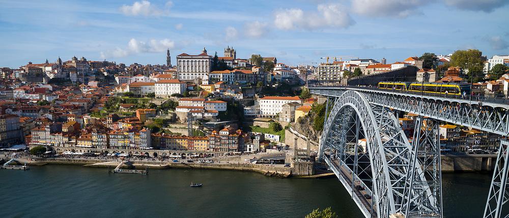 Rabelo port wine barge and The Ponte de Dom Luis I - metal arch bridge over River Douro connecting Porto to V|la Nova de Gaia, Portugal