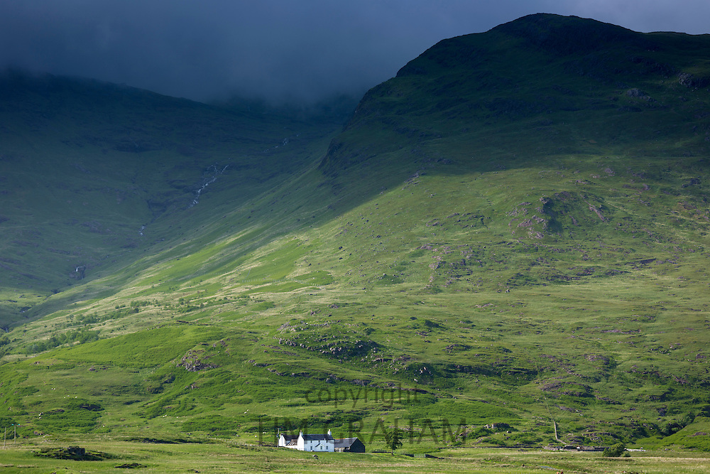 Small white solitary croft farmhouse nestling below mountain range by loch under moody sky on Isle of Mull in the Inner Hebrides and Western Isles of Scotland