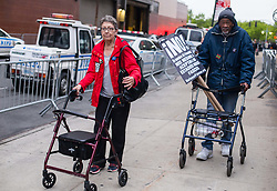 May 4, 2017 - Manhattan, New York, U.S - Two protestors leave  a demonstration, assembled across the street from the Intrepid Sea, Air & Space Museum, where the President spoke Thursday night. (Credit Image: © Nancy Siesel via ZUMA Wire)